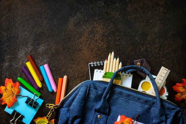 学校のコンセプトに戻る青いバックパック付きの学用品上面図