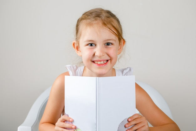 学校のコンセプトに戻る側面図。本を保持している小さな女の子。