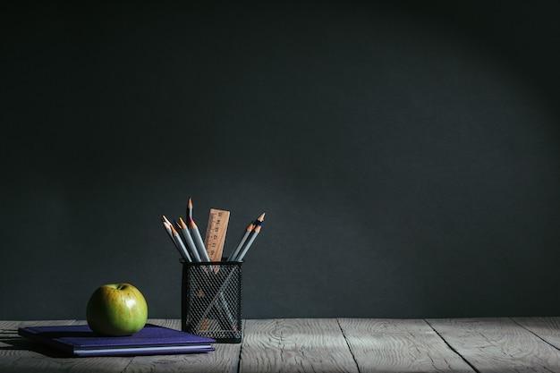 Снова в школу концепции. канцелярские товары с фруктами на столе