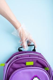 学校のコンセプトに戻ります。コロナウイルス感染の概念、学校での検疫、学校のサッチェルを持っている手袋をはめた手