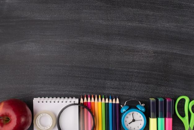 학교 개념으로 돌아가기. 빈 카피스페이스가 있는 칠판에 격리된 사과 시계와 다채로운 편지지의 오버헤드 뷰 사진 위