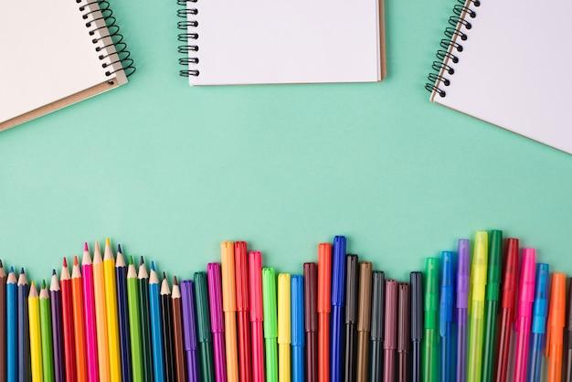 학교 개념으로 돌아가기. 청록색 배경에 격리된 다채로운 크레용 펜 마커와 빈 공책의 오버헤드 뷰 사진 위