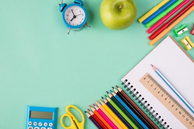 Снова в школу концепции. вверху над головой вид фото красочных школьных канцелярских принадлежностей синих часов и яблока, изолированных на бирюзовом фоне с copyspace