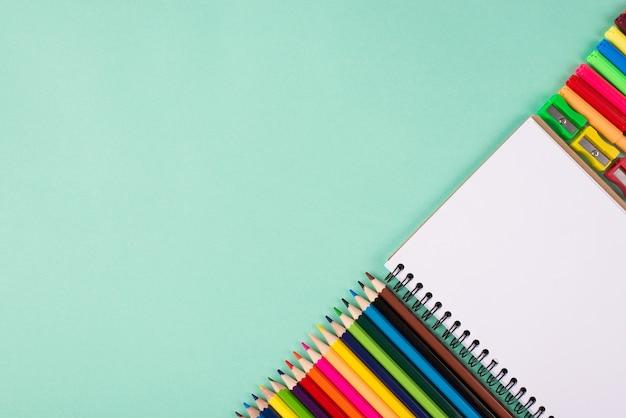 Снова в школу концепции. фотография красочных школьных канцелярских принадлежностей, изолированных на бирюзовом фоне с copyspace