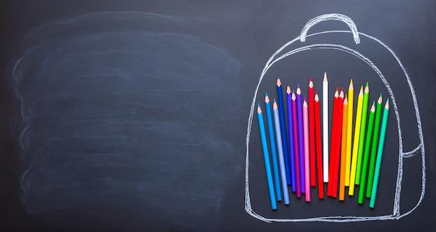 Обратно в школу концепция вид сверху рюкзака с цветными карандашами