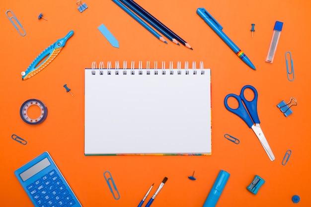 Обратно в школу концепция вид сверху школьные принадлежности на школьной партой на оранжевом фоне