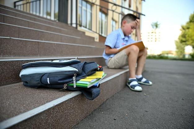 Снова в школу концепции. расстроенный взволнованный мальчик с рюкзаком делает домашнее задание. школьная сумка с копировальными книгами и школьными принадлежностями, лежащими на лестнице. вернуться к школьной концепции