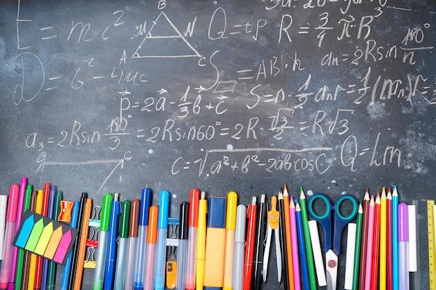 Обратно в школу, широкая граница с красочными школьными принадлежностями на фоне доски с математическими формулами