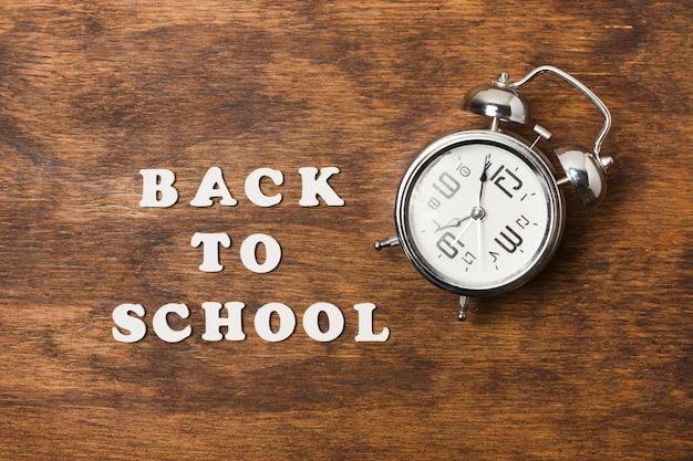木製の背景上の時計と学校の概念に戻る