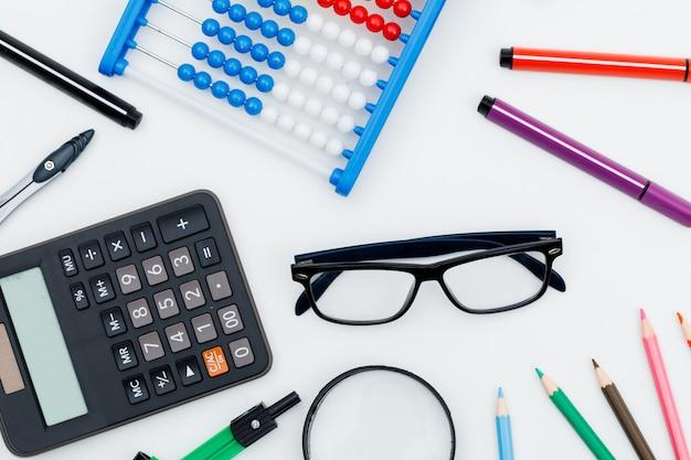 Обратно в школу концепции с увеличительным стеклом, очки, школьные принадлежности, калькулятор на белой стене плоской планировки.