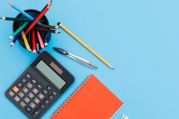 ノートブック、鉛筆、電卓、平らな青色の背景にコンパスで学校のコンセプトに戻る。