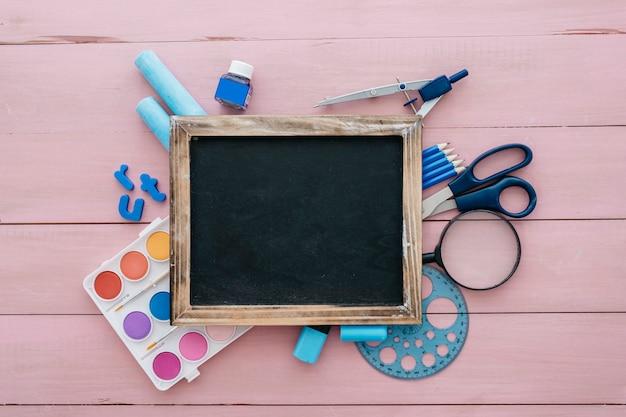 スレートと芸術のオブジェクトを持つ学校のコンセプトに戻る