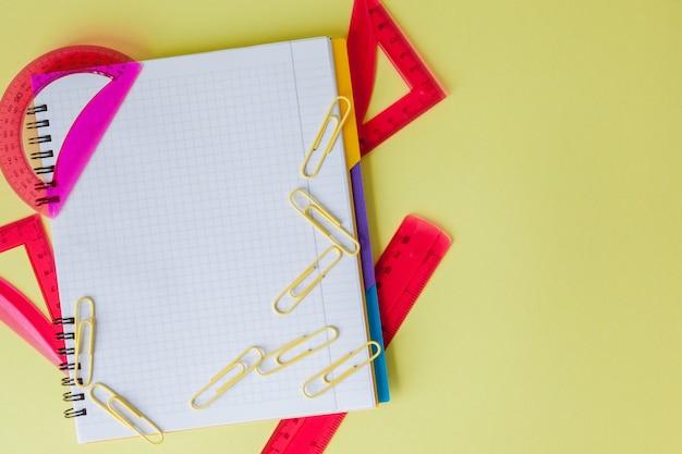 Снова в школу концепции с пространством для текста. вид сверху. скопируйте пространство. школьные канцелярские товары. творческий стол с красочными канцелярскими принадлежностями. цветная скрепка. школьные принадлежности на желтом фоне. офисный стол.