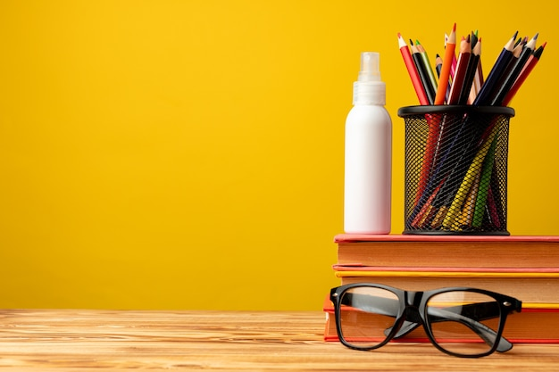 Обратно в школу с канцелярскими принадлежностями в чашке и антисептическим спреем для рук на желтом фоне