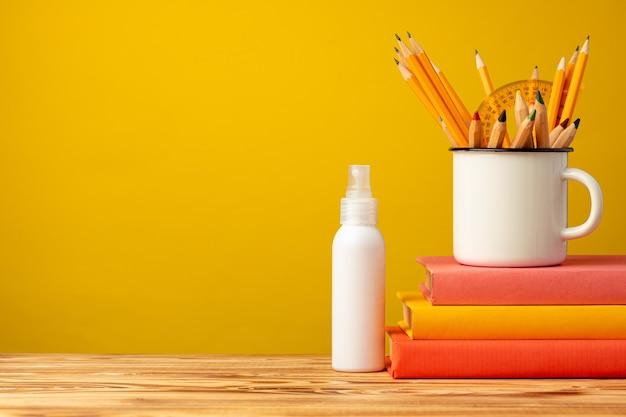 Снова в школу с канцелярскими принадлежностями в чашке и антисептическим спреем для рук против желтого