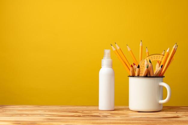 Снова в школу с канцелярскими принадлежностями в чашке и антисептическим спреем для рук на желтом