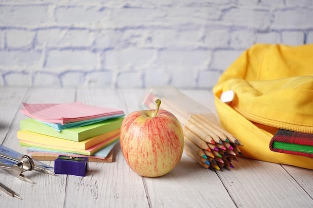 テーブルの上に黄色のバックパックと学校のサプライヤーと学校に戻るコンセプト