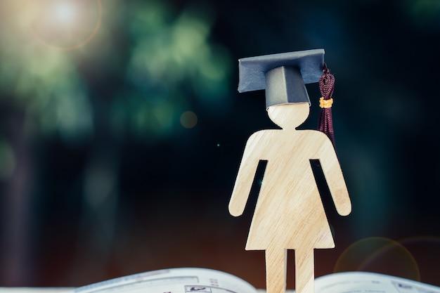学校に戻るコンセプト女性は開いた教科書に卒業帽で木に署名します