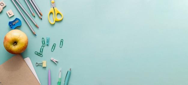 Снова в школу концепции. деревянные цветные карандаши, пустая школьная тетрадь, скрепки, яблоко и другие канцелярские товары на синем фоне. карандаши для рисования, предметы для творчества. макет