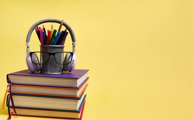 Вернемся к школьным концепциям. день учителя. композиция из стопки красочных книг карандаши очки беспроводные наушники на желтом фоне с копией пространства