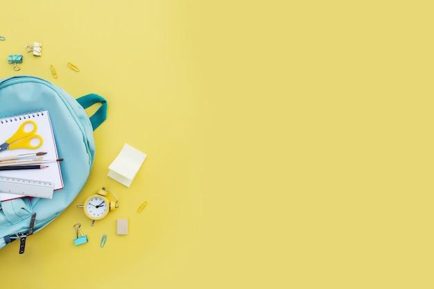 학교 개념적 평면으로 돌아가 다른 사무용품 품목과 텍스트를 위한 복사 공간이 있습니다. 초등 및 중등 학교 학생을 위한 개념입니다. 다양한 사무용품이 있는 학생 파란색 백팩 가방