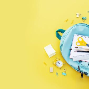 Снова в школьную концептуальную квартиру с различными канцелярскими товарами и копией пространства для текста. концепция для ученика начальной и средней школы. сумка для школьников синего цвета с разнообразными канцелярскими товарами
