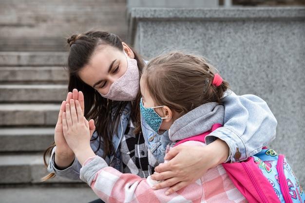Обратно в школу. дети пандемии коронавируса ходят в школу в масках. дружеские отношения с мамой. детское образование.