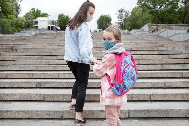 学校に戻る。コロナウイルスのパンデミックの子供たちはマスクをして学校に行きます。母との友好関係。