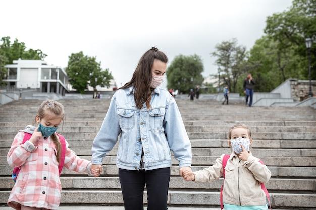 Обратно в школу. дети пандемии коронавируса ходят в школу в масках. дружеские отношения с мамой.
