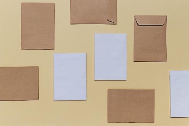 学校に戻るクリエイティブなコンセプト。黄色い紙の背景に白とベージュの封筒で空白のモックアップ。ミニマリストのフラットレイ、トップビューの構成。