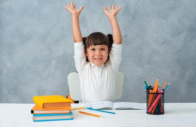 Обратно в школу. милый ребенок школьница сидит за столом в комнате.