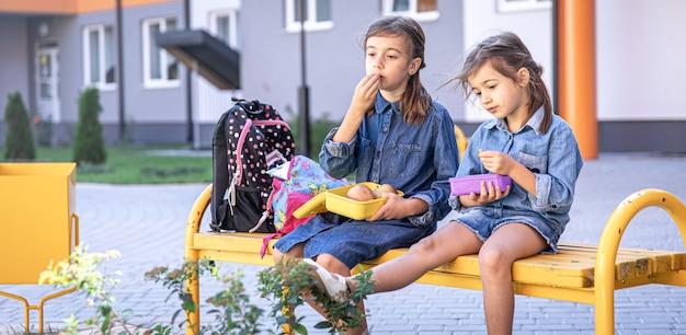 Обратно в школу. симпатичные маленькие школьницы сидят на скамейке в школьном дворе и едят обед на открытом воздухе.
