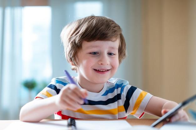 Обратно в школу дистанционное обучение онлайн-образование кавказская улыбка мальчик учится дома с