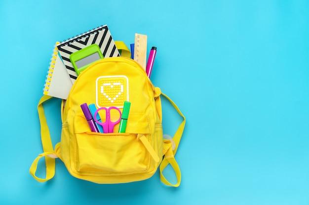 学校に戻って、教育の概念。学用品-ノート、ペン、定規、電卓、青色の背景に分離されたはさみと黄色のバックパック。上面図。