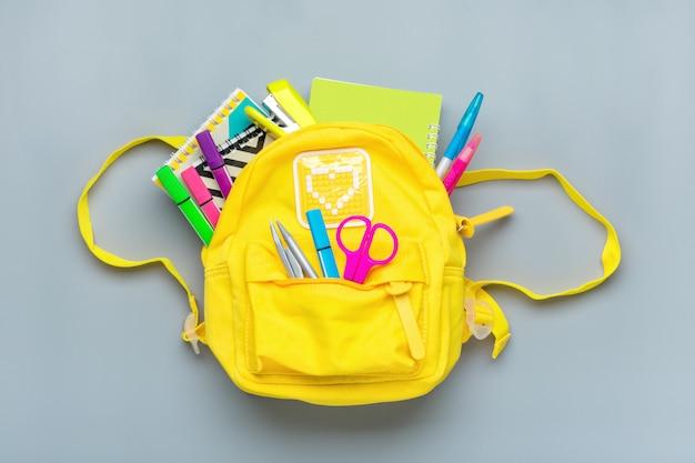 Обратно в школу, концепция образования. желтый рюкзак с школьных принадлежностей - тетрадь, ручки, правитель, калькулятор, ножницы изолированные на серой поверхности. вид сверху.