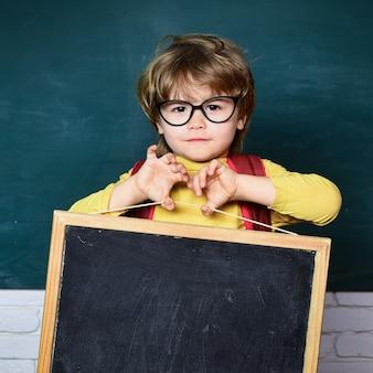 学校に戻る-教育の概念。教室でかわいい小さな就学前の子供の男の子。反対の学校の子供たち
