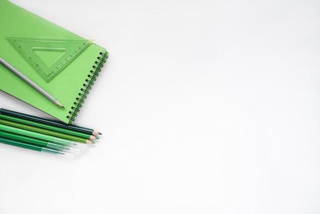 Обратно в школу. плоский лежал зеленый блокнот, карандаш на белом фоне с копией пространства. фон баннера