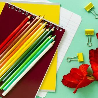 Вернуться в школу. различные канцелярские товары с цветами на мятном столе.