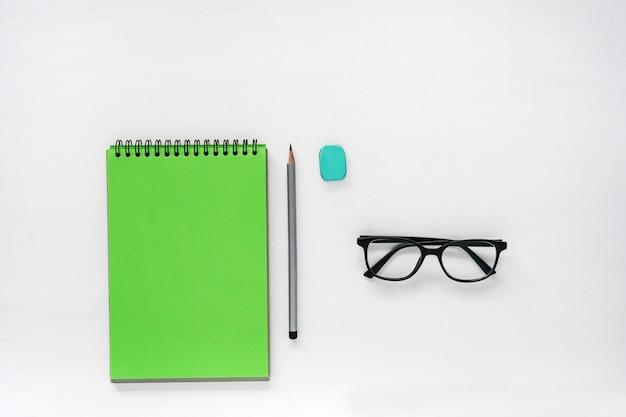 Обратно в школу. плоский макет зеленый блокнот, карандаш, очки на белом столе с копией пространства
