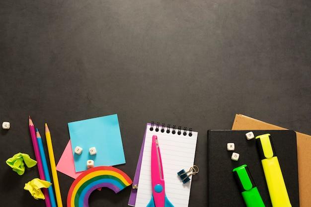 ノートブック、カラフルな鉛筆、マーカー、粘着紙などの事務用品を備えた学校のフレームに戻ります。