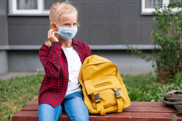 学校に戻る。マスクとバックパックを身に着けている女の子はコロナウイルスから保護し、安全です。パンデミックが終わって学校に通う子供。
