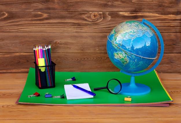 Обратно в школу! глобус, модель земли, учебный материал на деревянном столе.