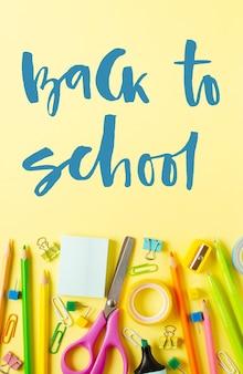 학교로 돌아가다. 손으로 쓴 비문. 노란 종이 바탕에 학용품이 있습니다.