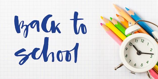 学校に戻る。手書きの碑文。白い市松模様の紙に学用品。