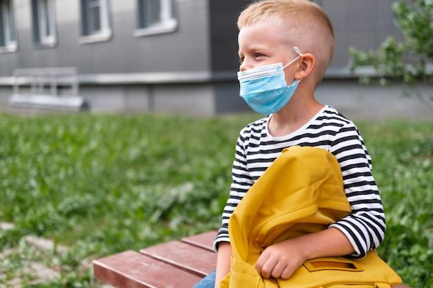 학교로 돌아가다. 마스크와 배낭을 착용하는 행복한 소년은 코로나 바이러스로부터 보호하고 안전합니다. 전염병이 끝난 후 학교 근처에 앉아있는 아이.