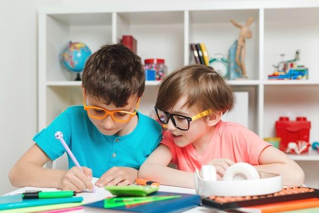 학교로 돌아가다. 책상에 앉아 숙제를하는 행복한 아이들. 쓰기와 읽기 수업에서 초등학교의 학생. 가정에서의 가정 교육 및 교육. 교실에서 수업에서 소년.