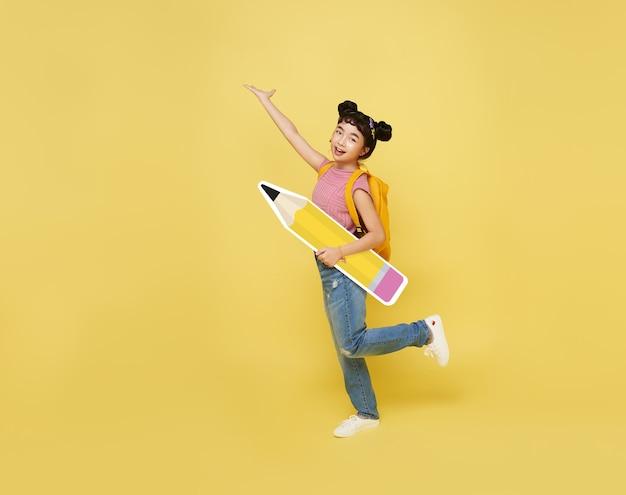 학교로 돌아가다. 노란색 벽에 연필을 들고 큰 배낭 행복 귀여운 아시아 아이. 교육 개념.