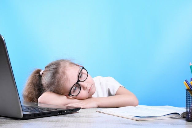 Обратно в школу. счастливый милый трудолюбивый ребенок сидит за столом в помещении. малыш учится в классе дома с ноутбуком, компьютером