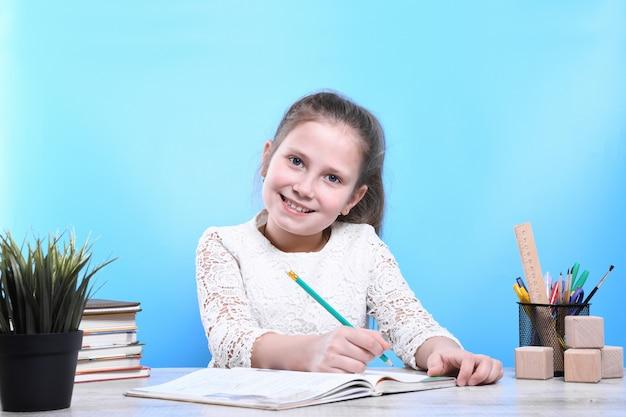 Обратно в школу. счастливый милый трудолюбивый ребенок сидит за столом в помещении