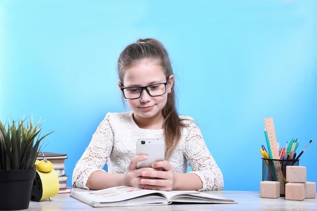 다시 학교로. 행복하고 귀여운 부지런한 아이가 실내 책상에 앉아있다.